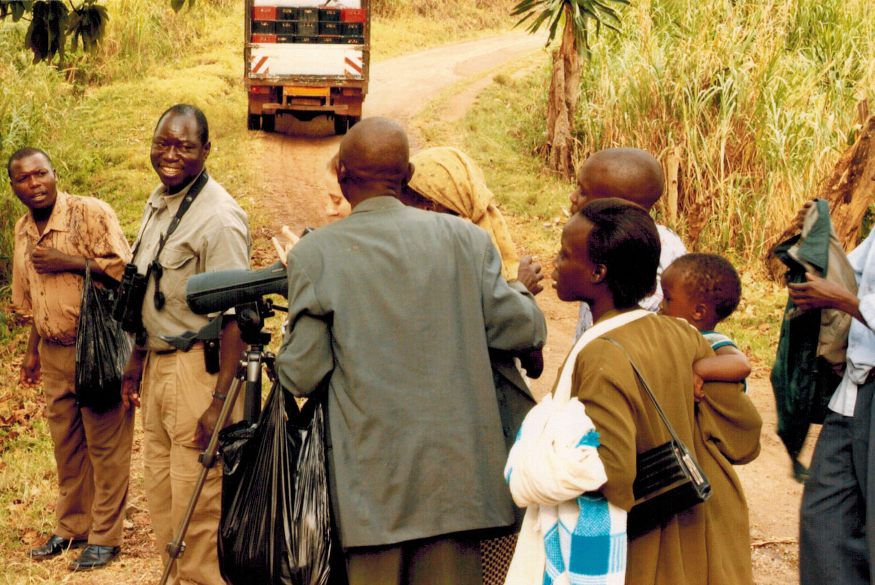 Guide Ben with Ugandan villagers looking at wildlife through our spotting scope