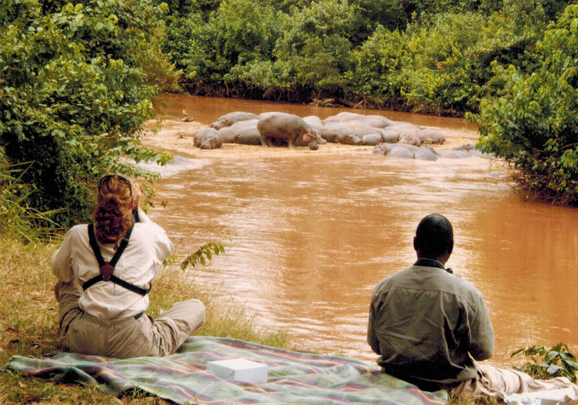 Christi and guide Ben watching hippos in in Murchison Falls National Park